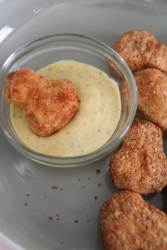 frozen chicken nuggets with honey mustard on the side.