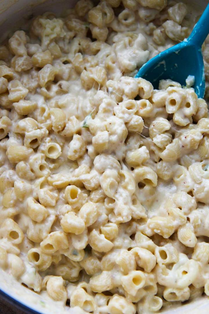 creamy spicy macaroni and cheese in a large pot with a blue spoon.