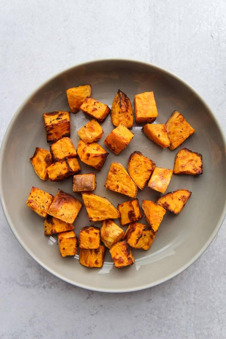 air fryer sweet potato cubes on a gray plate.