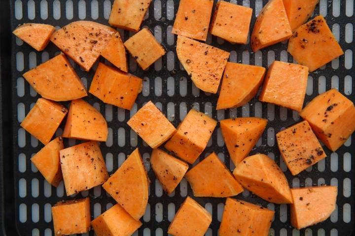sweet potato cubes on an air fryer tray.