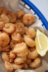 popcorn shrimp in a blue basket with a lemon wedge on the side.