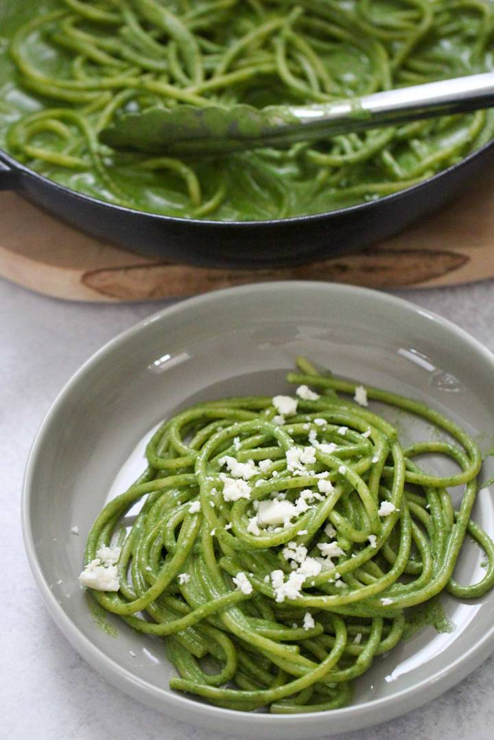 green noodles on a plate and a skillet.