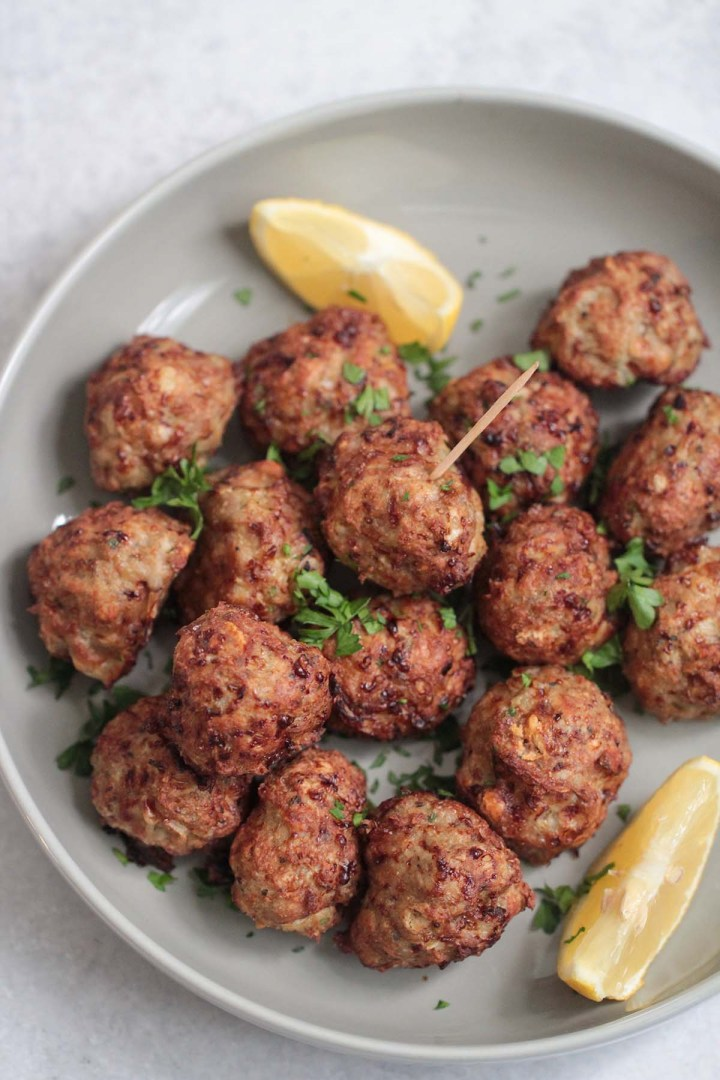 cooked air fryer turkey meatballs on a gray plate with lemon wedges and parsley.