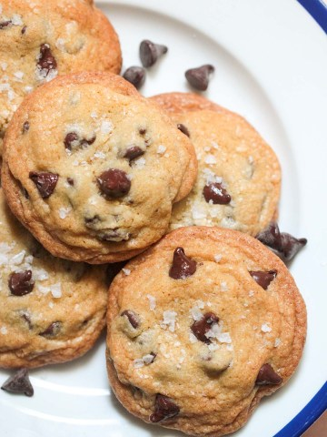 five brown butter chocolate chip cookies on a plate.