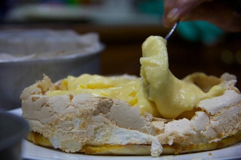 Mausie spoons lemon curd onto the lemon meringue cake