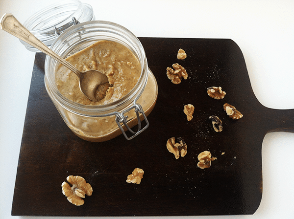 jar of homemade walnut butter with a spoon in it