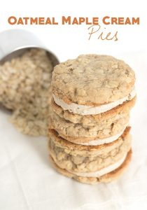 stack of sandwich cookies with a measuring cup full of oats behind it