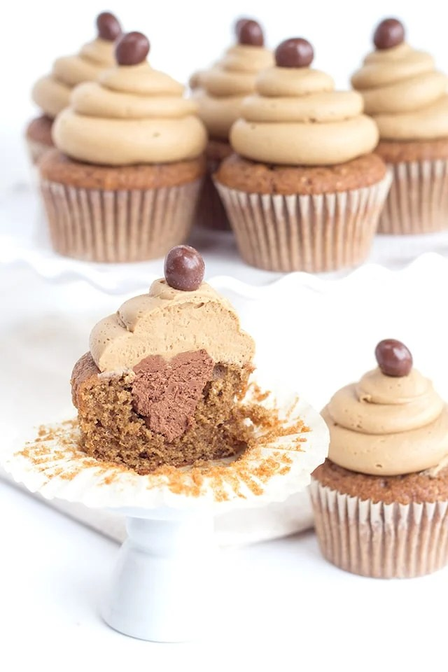 image of coffee cupcakes with coffee buttercream frosting - one cupcake is cut in half