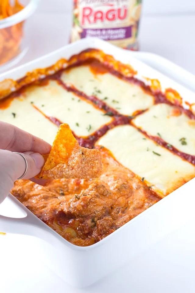 dipping tortilla chips into cheesy lasagna dip
