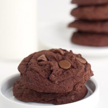 two double chocolate chip pudding cookies on a white plate with a stack of cookies in the background