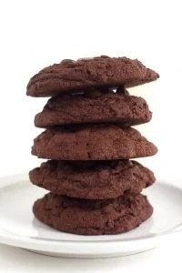 A stack of double chocolate chip pudding cookies on a white plate