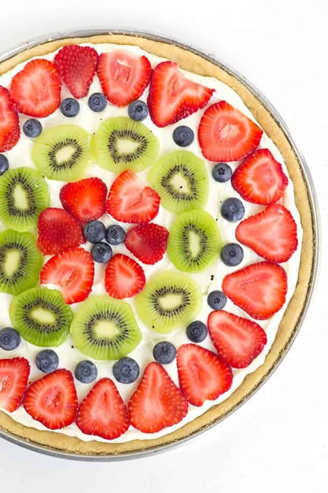 Easy Fruit Pizza - layers of sugar cookie, lemony cream cheese, and freshly sliced fruit! It's the perfect summer dessert pizza!