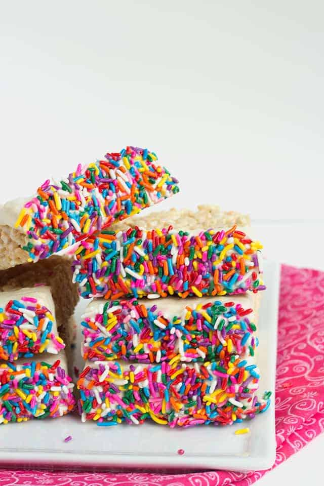 Chocolate Dipped Rice Krispie Treats - classic rice krispie treats dipped in chocolate and the ends are coated in loads of colorful sprinkles! A huge hit at any bake sale!