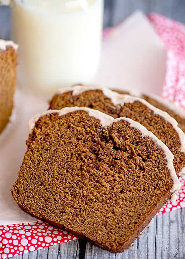 slices of gingerbread loaf on pink fabric with a glass of milk