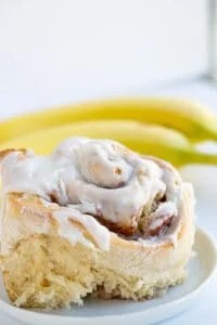 closeup of bananas foster cinnamon rolls on a white plate with frosting and a banana sitting next to it