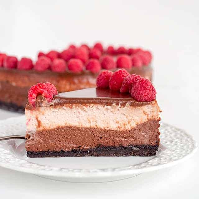 slice of chocolate raspberry cheesecake on a white dessert plate