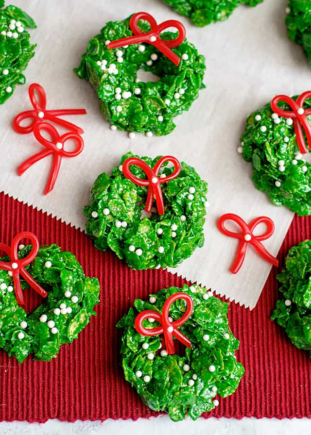 Christmas wreath cookies on parchment paper and red linen with candy bows around them