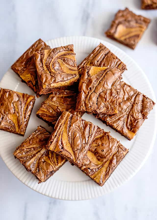 overhead view of pumpkin swirled brownies on a white cake plate and a marble background