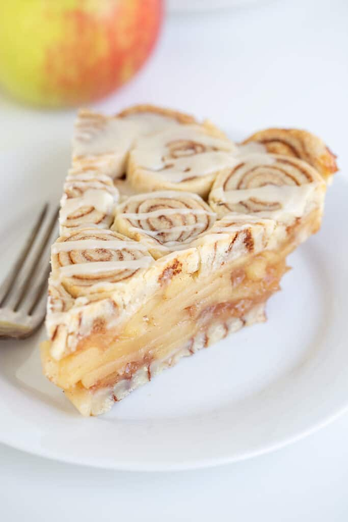 slice of cinnamon roll apple pie on a white plate with a fork
