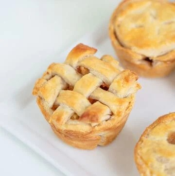 mini apple pie with lattice crust on a white platter with a green apple in the background