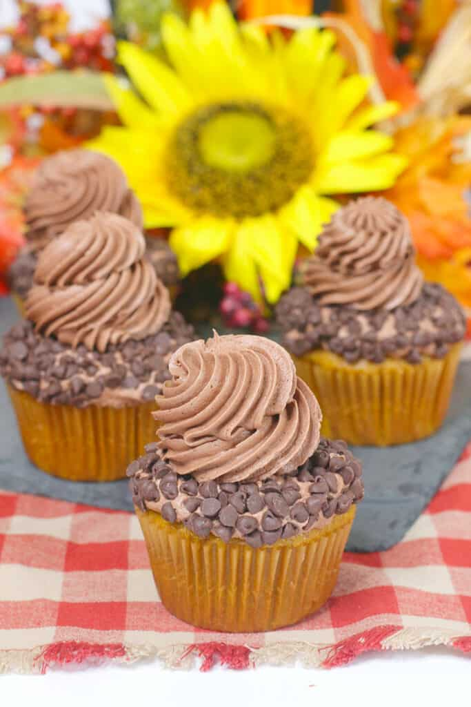 a cupcake with other cupcakes behind it on a dark slate board and flowers behind the cupcakes