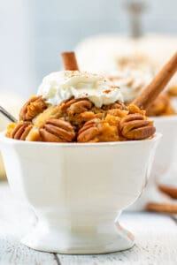 white serving dish filled to the top with pumpkin cobbler, pecans, and whipped cream