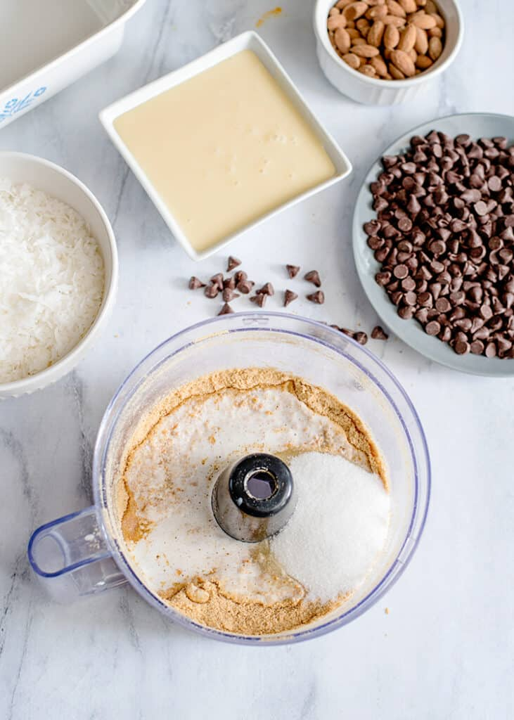 food processor with graham crackers, butter, and sugar in it with other ingredients around it