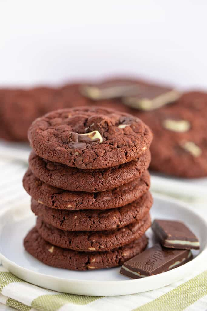 stack of chocolate cookies with andes mints beside the stack and a striped linen under the cookies
