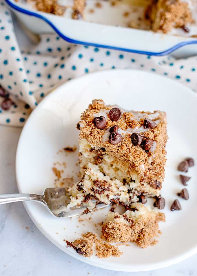 coffee cake on a white plate with chocolate chips and a fork