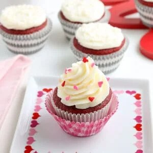 square image of a valentine's day themed red velvet cupcake on a white square plate