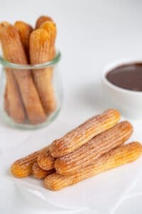 side view of the stacked air fryer churros on parchment paper with a jar of churros and a bowl of chocolate sauce behind it