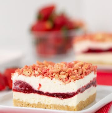 slice of dessert on a square plate sitting on a red fabric with strawberries in the background