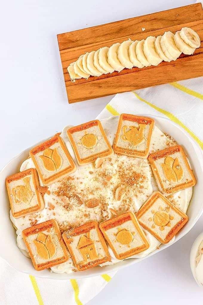 dish full of banana pudding with cookies on top and a board with sliced bananas