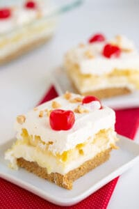 slice of banana split cake on a white plate with a red linen under it