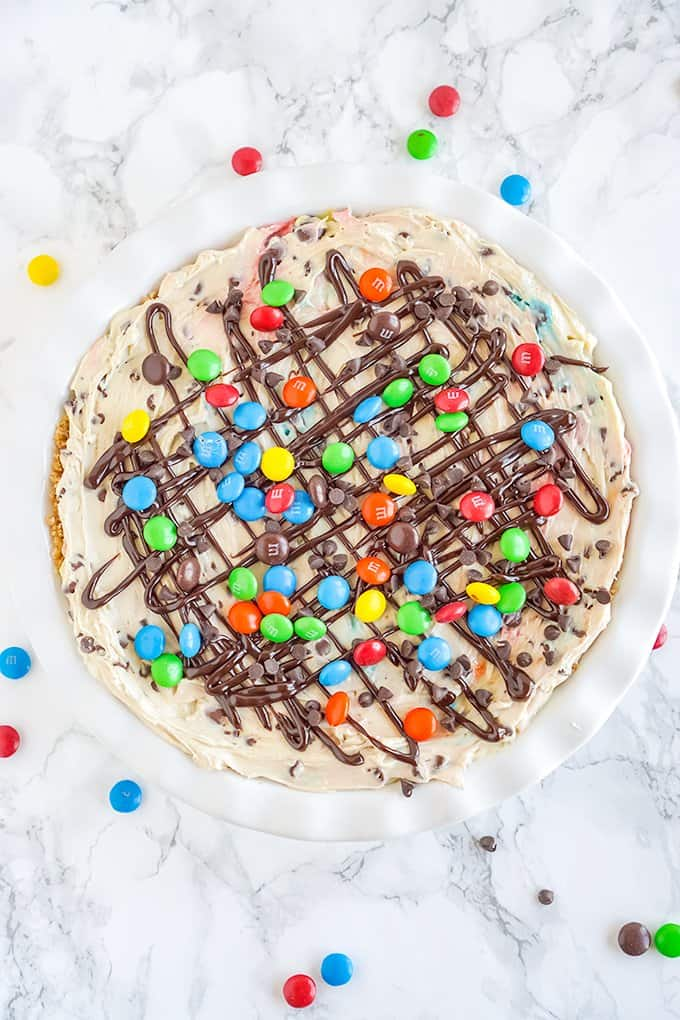 overhead photo of the cheesecake on a marbled surface with candies all around it