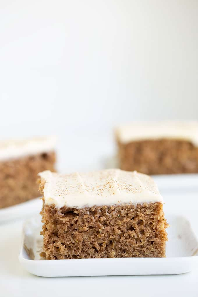 close up of a slice of zucchini cake on a white plate with other slices of cake behind it