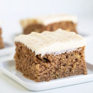 Square image of a zucchini cake on a white dessert plate on a white surface