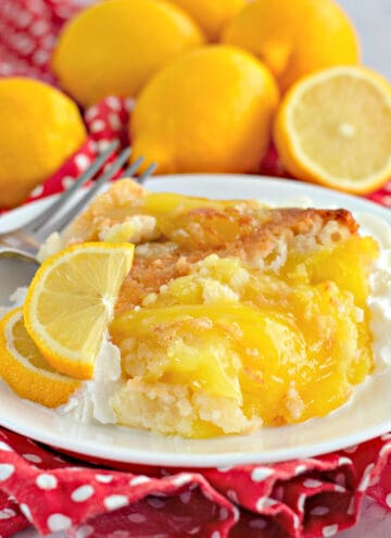 upclose picture of lemon cobbler on a white plate with fresh lemon slices and a fork