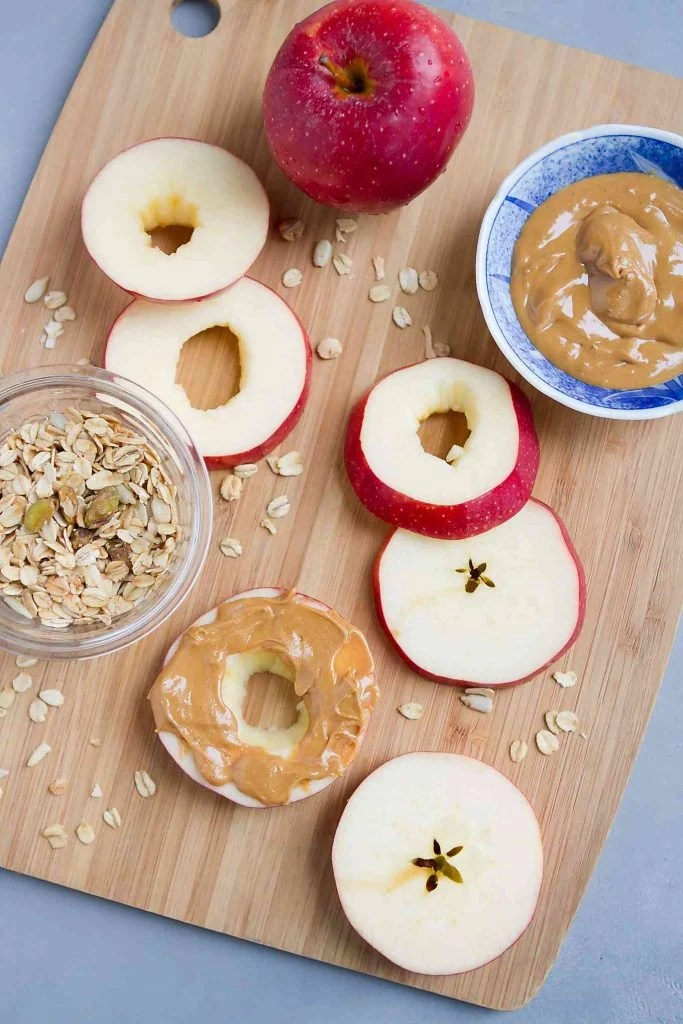 Apple rings, granola and peanut butter on a cutting board.