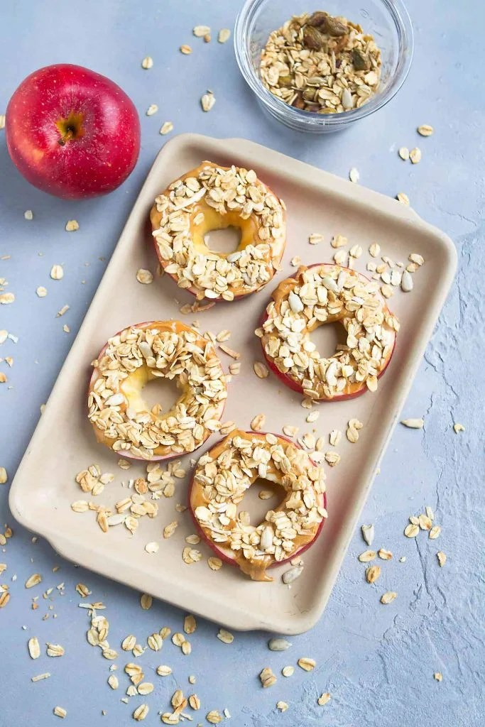 Apple with peanut butter and granola on a ceramic baking dish.