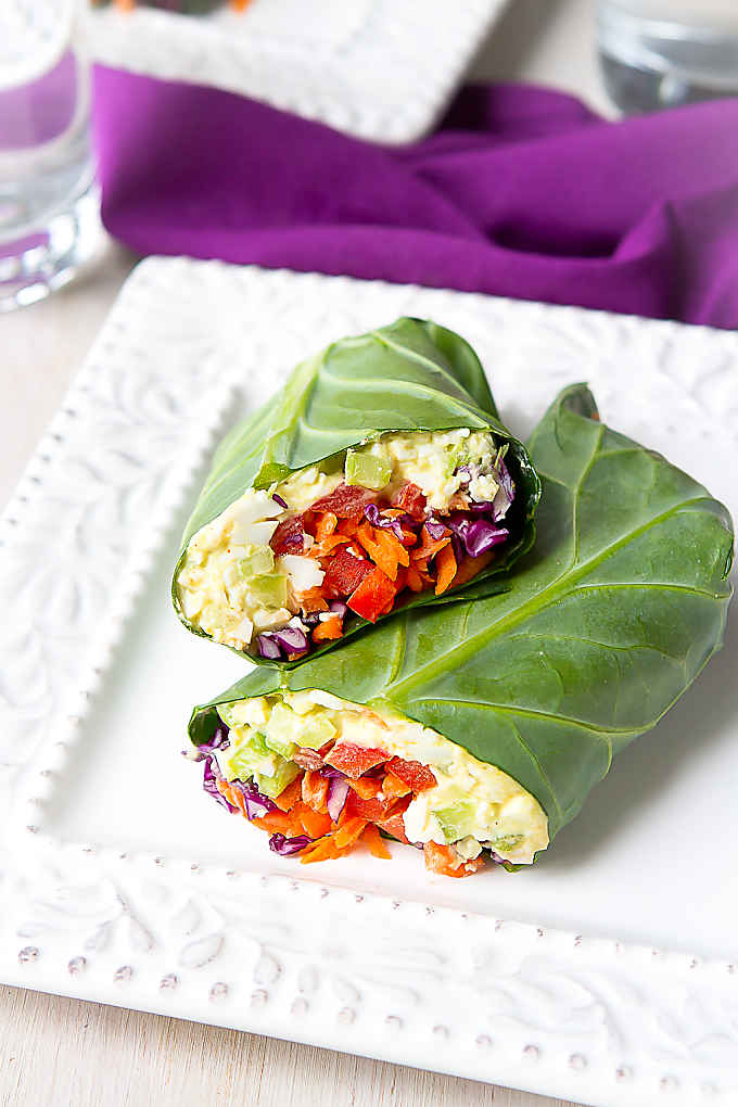 Egg salad collard green wraps with vegetables on a white plate.