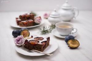 Schokoladen Zwetschgenfleck auf weißem Teller mit Kaffee in weißer Tasse, Zwetschge, violette Blüte