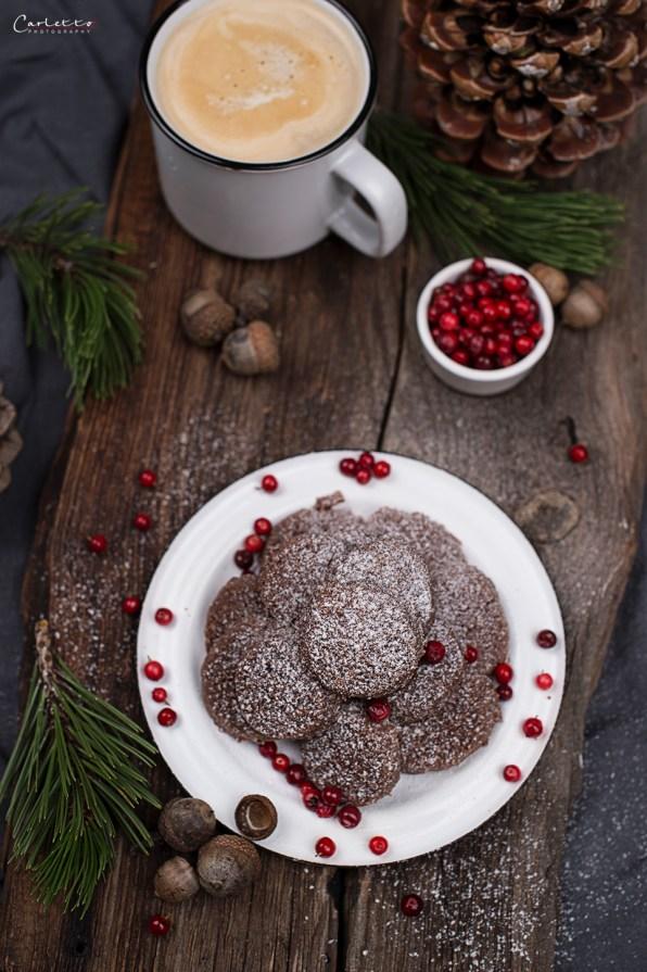 Schokoladen-Cookies mit Bröseln, Staubzucker auf weißem Teller mit Preiselbeeren auf Brett mit Kafee
