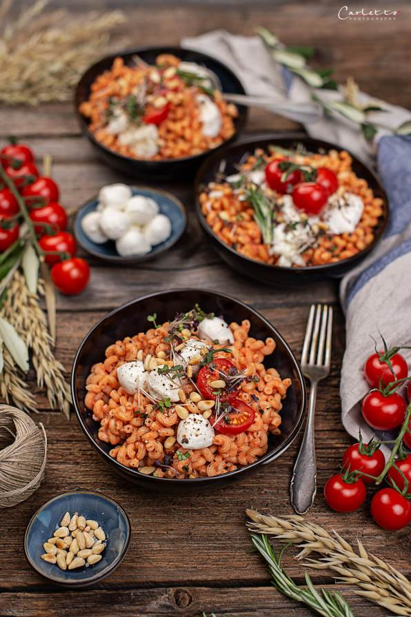 Dunkle Steingut-Schüsseln mit gedrehten Nudeln in Tomaten-Ricotta-Sauce mit Mozzarella garniert