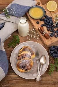 Drei Heidelbeerlaibchen mit Staubzucker auf einem grauen flachen runden Teller angerichtet