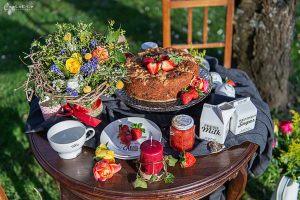 Picknick im Park - Holztisch mit zwei Stühlen, hübsch dekoriert mit Blumen, Kuchen