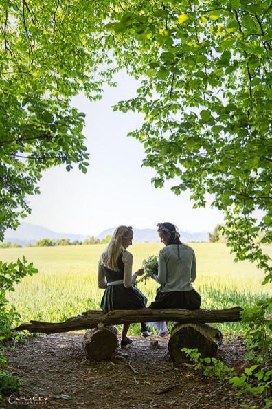 Dirdln im Dirndl auf einer kleinen Holzbank vor einem Getreidefeld