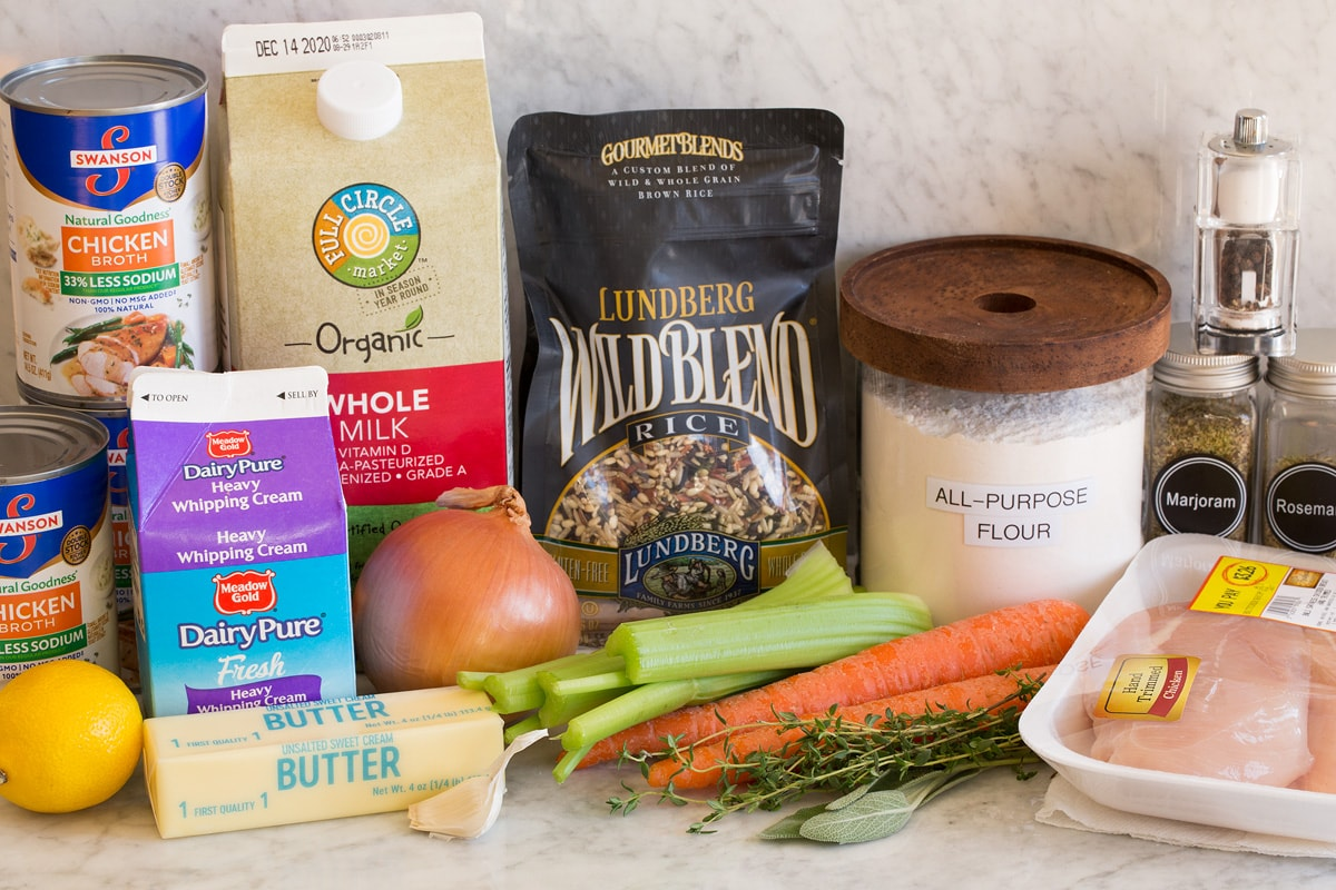 Image of the ingredients used to make chicken and wild rice soup. Contains wild rice, chicken breast, herbs, carrots, celery, onion, garlic, butter, milk, cream, lemon, flour, salt, pepper and chicken broth.