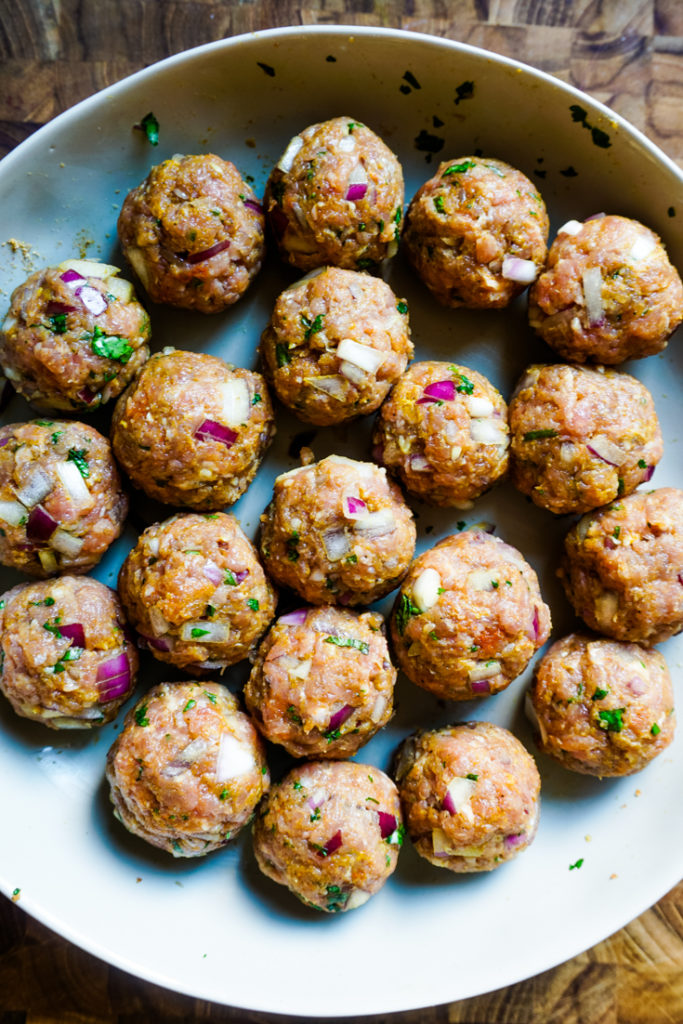 Meatballs ready to be cooked arranged in a white bowl