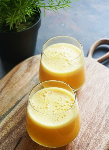 Two glasses of immunity boosting juice on a wood board